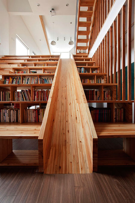 Playful wooden slide formed within a bookshelf