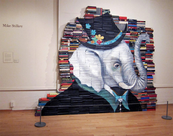 Mike Stilkey paints characters on stacks of books