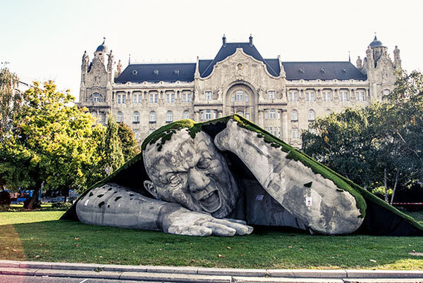 Sculpture of a giant man coming from under the ground